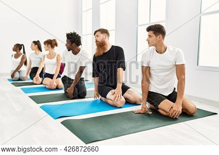 Group of young people concentrate stretching at sport center.