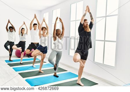 Group of young people concentrate training yoga at sport center.