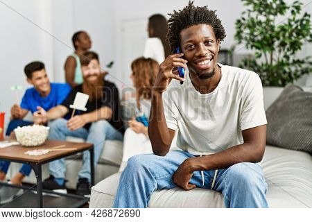 Group of young friends smiling happy sitting on the sofa. Man talking by the smartphone at home.