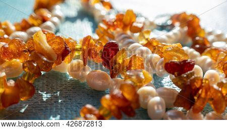 Sunny Beads Of Fire Amber Pearl Lapis Lazuli On Blue Backgroung. Natural Sea Gemstone Sunlight Backg