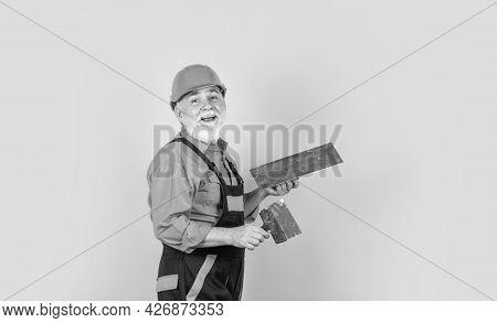 Plaster Trowel Spatula On Yellow Drywall Plasterboard. Plasterer In Working Uniform Plastering. Man