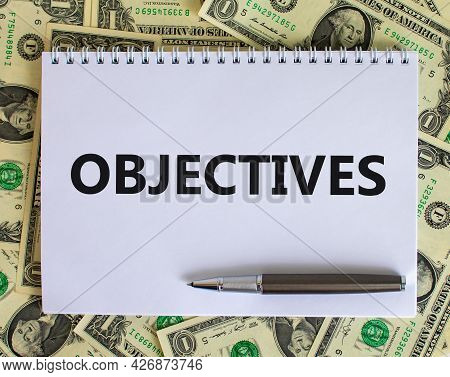 Objectives Symbol. The Word 'objectives' On White Note. Beautiful Background From Dollar Bills, Meta