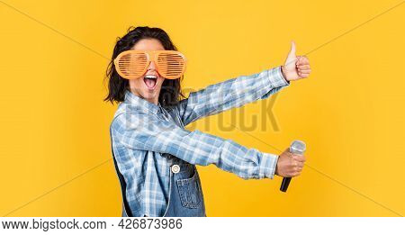 Smiling Female Hipster With Trendy Clothes Sing In Microphone, Event Manager