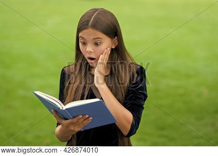 Surprise Helps To Study New Things. Surprised Child Read Study Book Outdoors. Knowledge And Informat