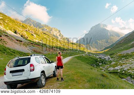 Young Caucasian Girl Observing The Mountain Landscape With Her White 4x4 Car During An Adventure Tri