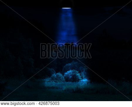 Sci-fi Concept Illustration. Unknown Flying Object Illuminating Forest Meadow With Blue Light During