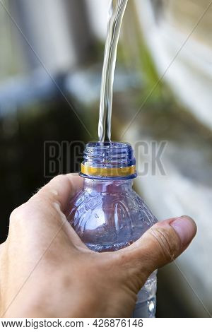 Caucasian Womans Hand With Blu Plastic Bottle. Girl Fills A Bottle With Fresh Pure Water In A Summer