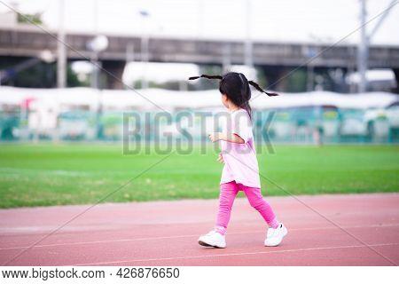 Cute Asian Girl Running Happily. Child Look Sideways. Kid Was Wearing Pink T-shirt And Leggings, Wea