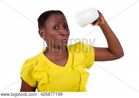 Young Girl Standing In Yellow Camisole Cup In Hand And Looking At The Camera With An Unpleasant Air.
