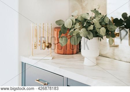 Clean kitchen with golden utensils on the countertop