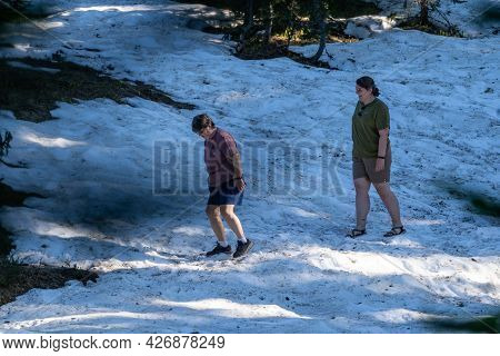 Washington, Usa - July 6, 2021: Two Woman Hikers Go Off Trail To Cross A Snow Field, In Mt Rainier N