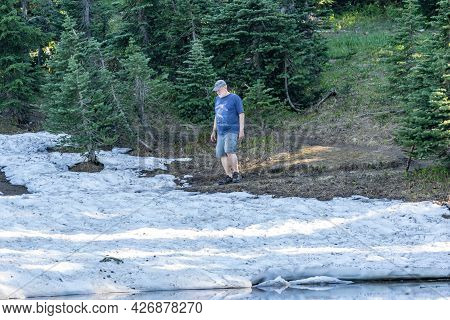 Washington, Usa - July 6, 2021: A Male Hiker Thinks About Going Off Trail To Cross A Snow Field, In