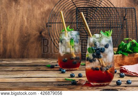 Blueberry Ice Mojito With Mint In Tall Glasses On Rustic Wooden Background.