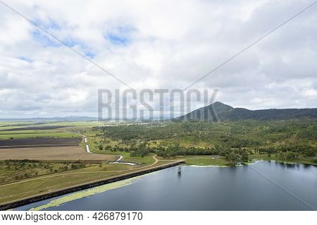 High Aerial Of Kinchant Dam Rock Wall, Water Catchment Area, And Farmland And Mountains Beyond. Quee
