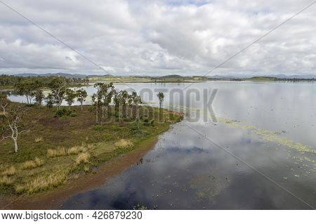 Aerial Of Unpopulated Land In A Dam With Cloud Reflections In The Calm Water. Kinchant Dam, Queensla