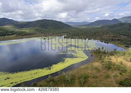 The Shore Of A Dam Lined With Green Plant Life On The Water And Cloud Reflections. Kinchant Dam, Que