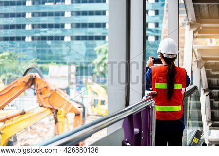 The Woman Foreman Is Standing To Monitor And Take Photo With Smartphone To Control The Demolition Of
