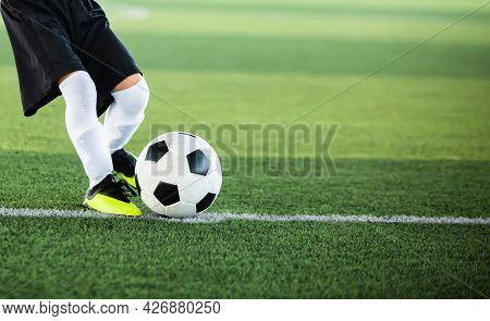 Selective Focus To Football With Motion Blur Of Kid Soccer Player Shoot It On Artificial Turf.