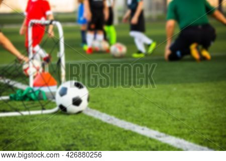 Blurry Soccer Ball With Kid Soccer Player And Soccer Training Equipment On Green Artificial Turf.