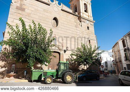 Tarbena Spain - August 26 2016; Green John Deere Tractor Parked In Narrow Village Street Outside Chu