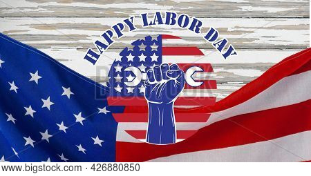 Happy labor day text over hand holding tool icon and american flag against wooden background. american labor day celebration concept