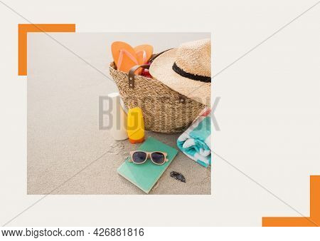 Photograph of basket with accessories at the beach against grey background. summer holiday and vacation concept