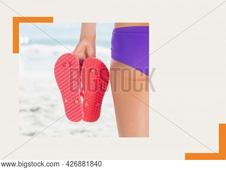 Photograph of mid section of woman holding flip flops at the beach against grey background. summer holiday and vacation concept