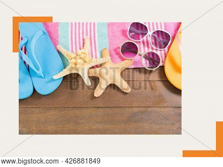 Photograph of flip flops, sunglasses and starfish on wooden surface against grey background. summer holiday and vacation concept