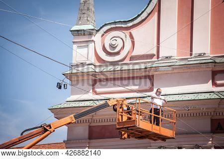 Ljubljana, Slovenia - June 15, 2021: Selective Blur On An Electrician, A Technician Worker Fixing An
