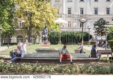 Belgrade, Serbia - June 26, 2021: Young Man And Old Senior Woman Sitting In Park Cirila I Metodija,