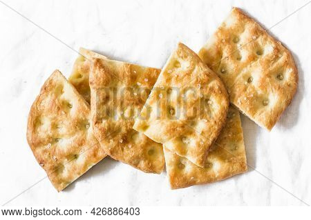 Italian Crunchy Focaccia On A Light Background, Top View. Traditional Italian Bread
