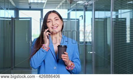 Serious Brunette Businesswoman With Long Loose Hair Talks On Black Smartphone And Holds Grey Plastic