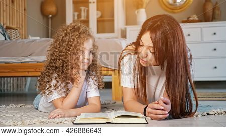 Smiling Mom Reads Fairytale From Book Lying On Floor Near Thoughtful Preschooler Daughter With Long