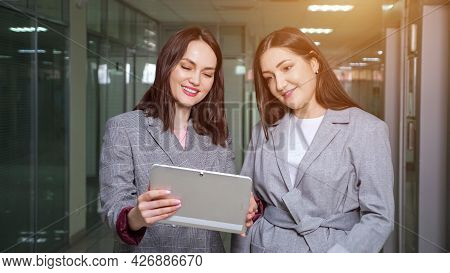 Company Manager Shows Reports Holding Grey Tablet In Hands To Brunette Director And Talking In Hallw