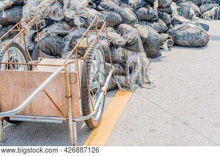 Two Wheeled Wooden Push Cart Parked In Front Of Fishing Nets Wrapped In Black Mesh.