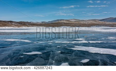 On The Smooth Blue Ice Of The Frozen Lake Lie Plots Of Snow. Deep Intersecting Cracks Are Visible. C