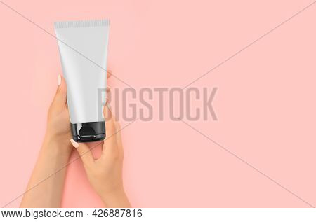 Hand Holding Mockup Cosmetic Plastic Tube Isolated On Pink Background. Cream Tube In Hand Cream On S