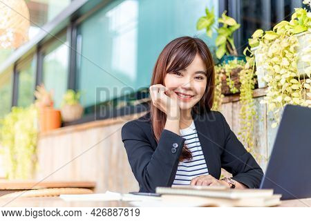Young Attractive Business Woman In Her Casual Suit Smiling At Camera While Working On Her Computer A