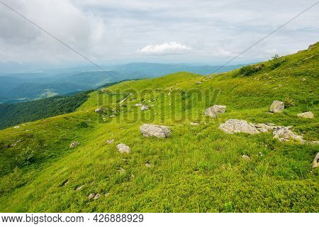 Green Nature Landscape In Mountains. Beautiful Travel Background In Summer. Stones On The Grassy Hil