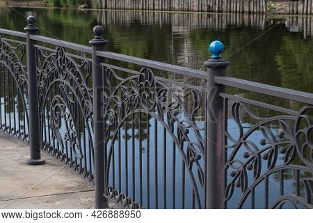 Painted Blue Ball Knob Post Of Black Fence With Wrought Iron Designs Of Gaps Between, Which Enclosin