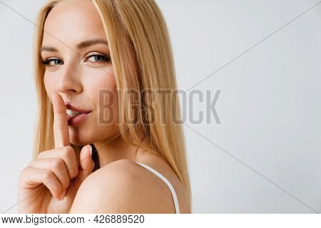 Young blonde woman showing silence gesture at camera isolated over white background