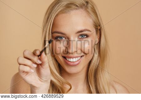 Smiling young white blonde woman with bare shoulders standing over beige background, holding eyebrow brush