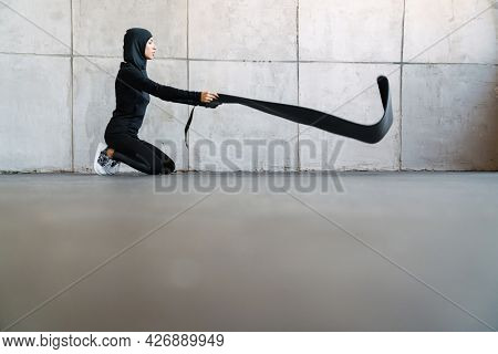 Young muslim woman in hijab unrolling fitness mat indoors