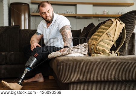 Mid aged white man with prosthetic leg sitting on a couch at home