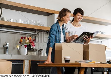 A laughing lesbian couple looking into a magazine and sorting boxes after moving in the light kitchen