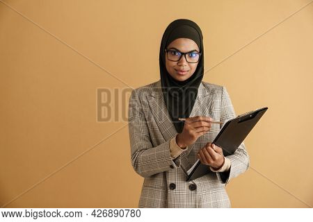 Black muslim woman in eyeglasses writing down notes on clipboard isolated over beige background