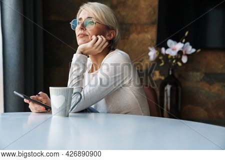 Upset disappointed young woman wearing casual clothes using mobile phone while sitting at the kitchen table with cup of coffee