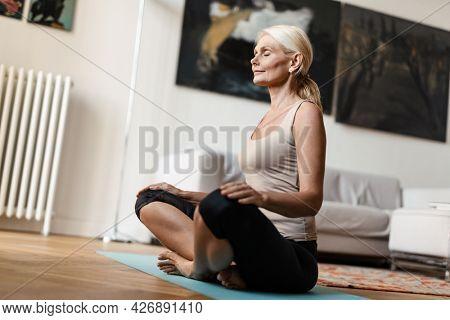 Blonde mature woman meditating during yoga practice at home