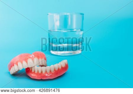 A Prosthesis And A Glass With A Solution. Dental Prosthesis Care. Full Removable Plastic Denture Of