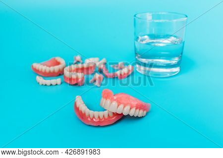 Dentures On A Blue Background. Close-up Of Dentures. Full Removable Plastic Denture Of The Jaws. Pro